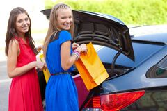 Two girls are piling the bags in the car. Two girls are piling the bags in the luggage compartment car Stock Photos