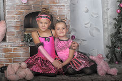 Two girls in pink for Christmas. Two girls sisters in pink in Christmas stock photography