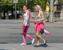 Two Girls in Pink Walking with Mobile Phones. OTTAWA, CANADA - AUGUST 26:  Two flamboyantly-dressed girls with mobile phones walking to the Capital Pride Parade Royalty Free Stock Photo