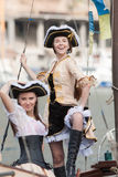 Two girls in pirate costumes outdoors. Two girls in pirates costumes posing on the deck of boat Royalty Free Stock Photo