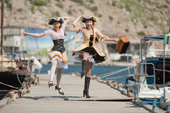 Two girls in pirate costumes outdoors. Two girls in pirate costumes are jumping Stock Photos