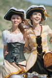 Two girls in pirate costumes outdoors. Two laughing girls in pirate costumes are walking outdoors Royalty Free Stock Photos