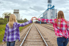 Two girls plaid shirts grain terminal Royalty Free Stock Image