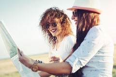Two girls planning their summer seaside road trip with convertible. Closeup picture royalty free stock photos