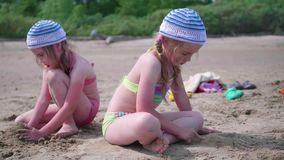 Two girls play on the beach making sand figures. Hot summer day. Family holidays by the sea. Child playing with sand on the beach stock video