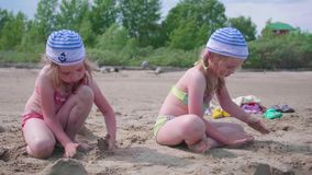Two girls play on the beach making sand figures. Hot summer day. Family holidays by the sea. Child playing with sand on the beach stock footage
