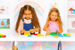 Two girls play with blocks in class Stock Photo