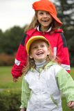 Two girls play with cap. Two child play with cap in autumn Stock Images