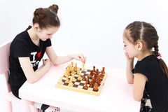 Two girls play chess. White bishop move. Stock Image