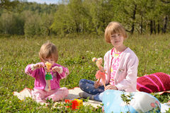 Two girls play with dolls Stock Images
