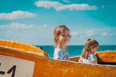 Two girls play in a fishing boat on the beach Stock Photo