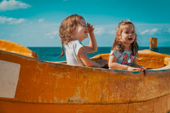 Two girls play in a fishing boat on the beach Royalty Free Stock Photography