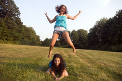 Two girls play leap frog. Two early twenties caucasian women play leap frog stock photos