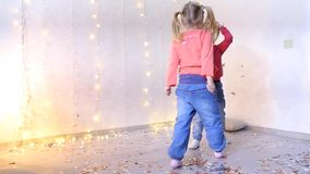 Two girls play in living room and pick up Christmas confetti from floor. Two beautiful girls playing in living room, children pick up confetti from floor and stock video footage