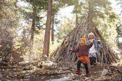 Two girls play outside shelter made of branches in a forest Stock Image