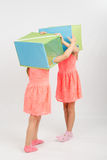 Two girls play about putting on a head box Royalty Free Stock Photography