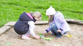 Two girls play in the sandbox. Two little girls play in the sandbox. Long shot stock footage