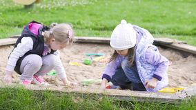 Two girls play in the sandbox. Two little girls play in the sandbox. Long shot stock video