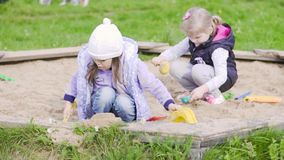 Two girls play in the sandbox. Two little girls play in the sandbox. Slow motion. Long shot stock video
