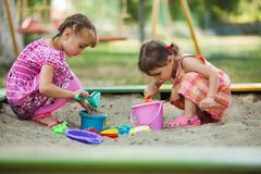 Two girls play in the sandbox. At the playground Royalty Free Stock Photo