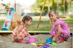 Two girls play in the sandbox. At the playground Stock Photography
