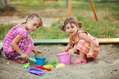 Two girls play in the sandbox Royalty Free Stock Photography