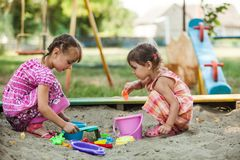 Two girls play in the sandbox. At the playground Royalty Free Stock Images