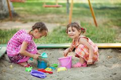 Two girls play in the sandbox. At the playground Stock Images