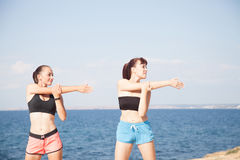 Two girls play sports fitness on the beach Royalty Free Stock Image
