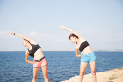 Two girls play sports fitness on the beach Royalty Free Stock Photo