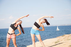 Two girls play sports fitness on the beach Stock Image