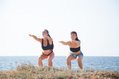Two girls play sports fitness on the beach Stock Photos