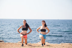 Two girls play sports fitness on the beach Royalty Free Stock Photos