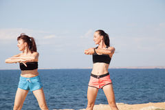 Two girls play sports fitness on the beach Royalty Free Stock Images
