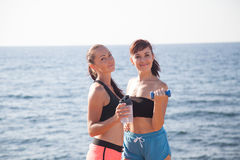 Two girls play sports fitness on the beach by the sea Royalty Free Stock Image
