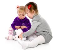 Two girls play with a teddy bear Stock Images
