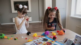 Two girls play with toys. Two pretty girls play indoor stock footage