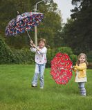 Two girls play with umbrella. Two childs play with umbrella Royalty Free Stock Image
