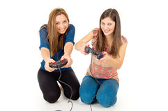 Two girls play video games. Two girls are playing video games isolated Royalty Free Stock Photography