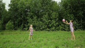 Two girls playing with the ball. Children play with a ball on the green field behind them and a lot of green forest trees stock video footage