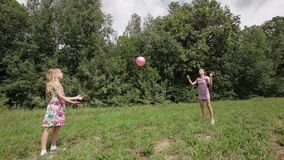 Two girls playing with the ball. Children play with a ball on the green field behind them and a lot of green forest trees stock footage