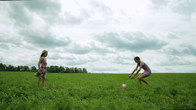Two girls playing with the ball. Children play with a ball on the green field many clouds cloudy stock video footage