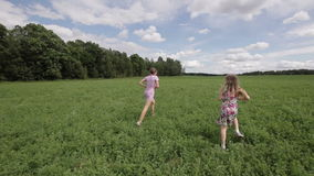 Two girls playing with the ball. Children run on the green field playing ball catch the ball with the behind them and a lot of green forest trees shot steadicam stock footage