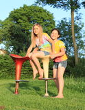 Two girls playing on bar chairs Royalty Free Stock Photos