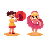 Two girls playing on beach with inflatable ring and ball Royalty Free Stock Images