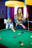 Two girls playing billiard Stock Images