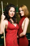 Two girls are playing billiards. Two beautiful girls are playing billiards stock images