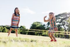 Two girls playing Chinese jumping rope in the park. Royalty Free Stock Image