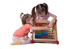 Two girls playing with colored bills sitting Stock Photos