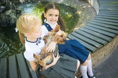 Two girls playing with a dog stock photo